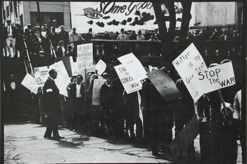 """Halifax anti-Vietnam War marchers assemble below a Moir's Chocolate billboard that says """"Some Good.""""  The Moir's factory was where the Trade Centre is today. Photo: Stephen Archibald"""