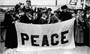 """Black and White photo from the early 1900s showing people holding a banner that says """"Peace."""""""