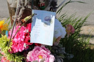 A Mother's Day card is attached to a memorial on Pleasant Street.