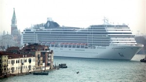 A massivelay large cruiseship dwarfs the buildings in Venice as it passes by.