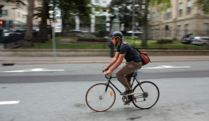 A cyclist with a backpack and helmet whizzes along a city street.