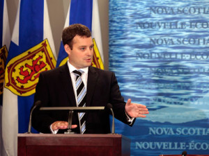 Man in suit at podium with Nova Scotia flag behind him.