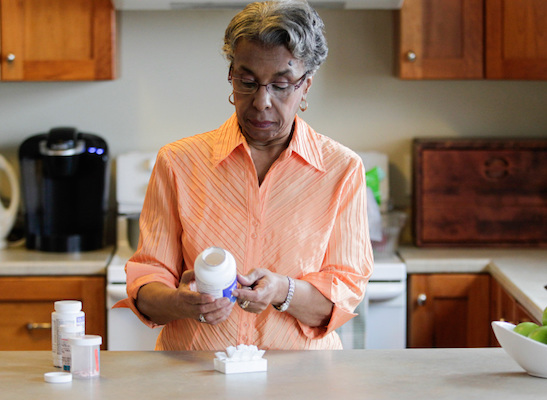The government included this photo of a confused elderly person trying to figure out her medication.