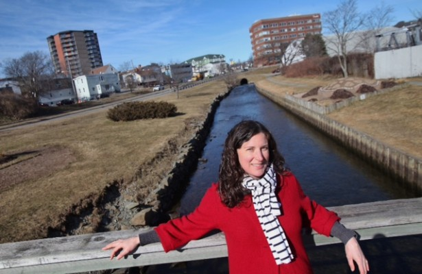 Jocelyne Rankin, water co-ordinator at the Ecology Action Centre, stands in front of the Sawmill River after it exits an underground culvert (seen in the distance) and flows in a channel to Dartmouth Cove. Photo: Tim Krochak / Local Xpress
