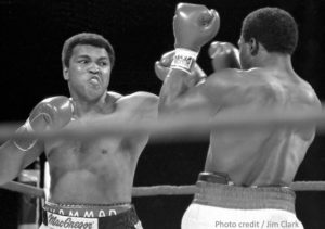 A black and white photo of the boxing match between Muhammad Ali and Trevor Berbick. ali is facing the camera, just about to land a left, and Berbick has his back to the camera and his gloves up.