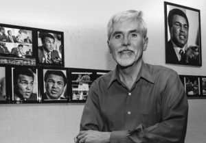 A black and white photo of Jim Clarke, standing in front of a wall displaying several of his framed photos of Muhammad Ali.