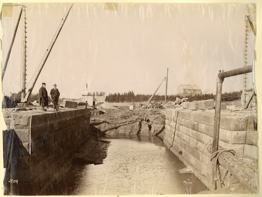 Two men standing on bridge abutment for Chignecto Ship Railway : close-up view showing metal pipes and rope in foreground and out-buildings, pulleys and houses in background. Photo: New Brunswick Archives