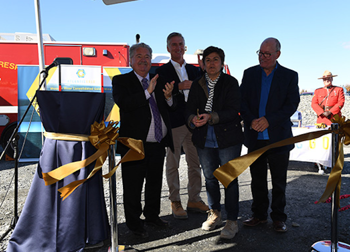 A photo of Lloyd Hines, Steven Dean, Maryse Belanger, and Terrance paul. They're standing in the shade under a big tent. Hines is clapping, the others are smiling happily. Belanger has just cut the shiny gold ribbon. In the background you can see an emergency response vehicle and a Mountie in his red serge, standing in the hot sun behind a table like a waiter, smiling intently towards the group.