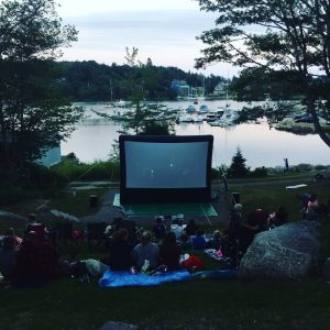 People watching a movie on an outdoor screen in Hubbards, with sailboats in the background.