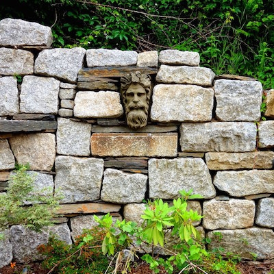 A photo of a stone head placed in a stone wall