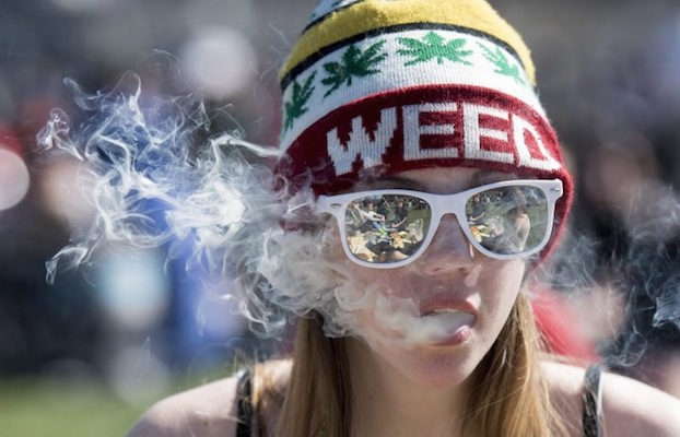 "A photo of a woman smoking pot while wearing a hat that says ""weed."""