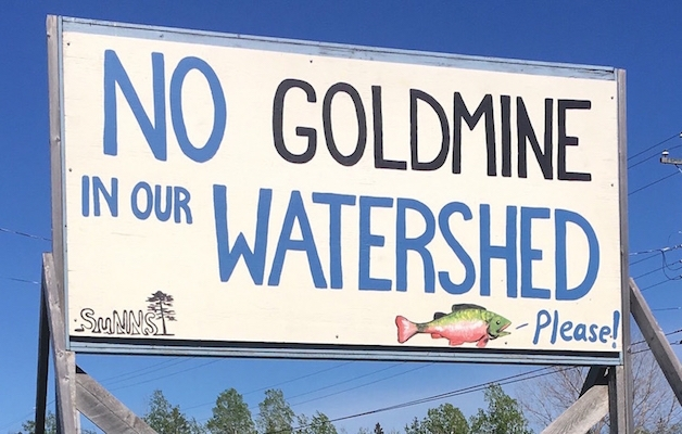 "A sign reading ""No goldmine in our watershed, please"""