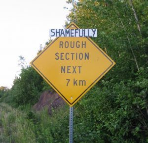 "A road sign reading ""Rough Section Next 7 km"" has a handwritten sign saying ""shamefully"" posted above it."
