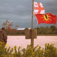 Man by Shubenacadie River at the Alton Gas site, with Mi'kmaq and Warrior flags.