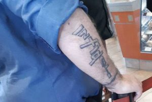 "Tattoo reading ""Infidel"" on the arm of a sailor."