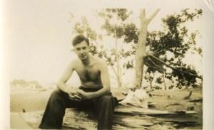 Young shirtless man on a log