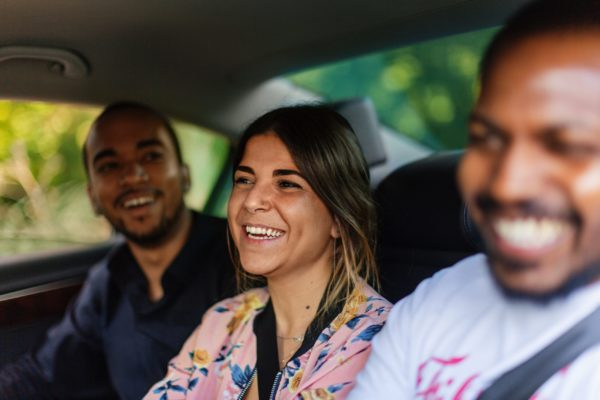 Three people smiling in the back seat of a car, presumably driven by an Uber driver.