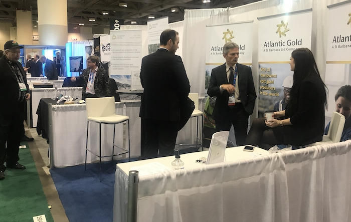 Atlantic Gold's booth at 2020 PDAC convention in Toronto. White tablecloths, white banners with the Atlantic Gold logo in black text and a gold (what else) logo. a man appears to be mansplaining something to a young woman, while a convention visitor listens..