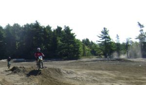 Dirt bike on a jump in a dirt pit.