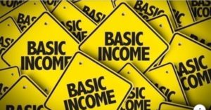 """A photo illustration of several yellow diamond-shaped signs with black capitalized text reading """"Basic Income"""""""