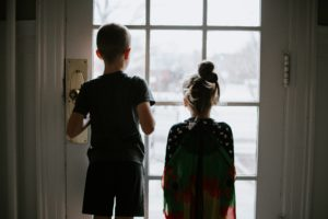 Two children stand at a door looking outside.