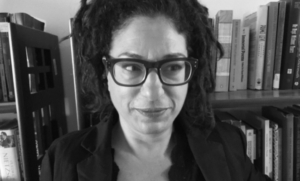 a black and white photo of Lissa Skitolsky. wearing a dark jacket, with dreadlockded hair and funky glasses, looking to her left