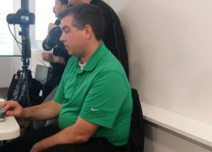 Dustin O'Leary is a white dude of indeterminate age, slouched at a table, wearing a bright green golf shirt with a white T shirt underneath. He's not smiling, he's just morosely playing with his laptop.