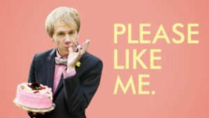 Actor Josh Thomas in a suit, holding a cake and licking his thumb.