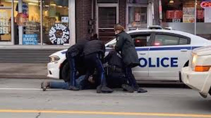 Police crowd around a man on the ground in the street.