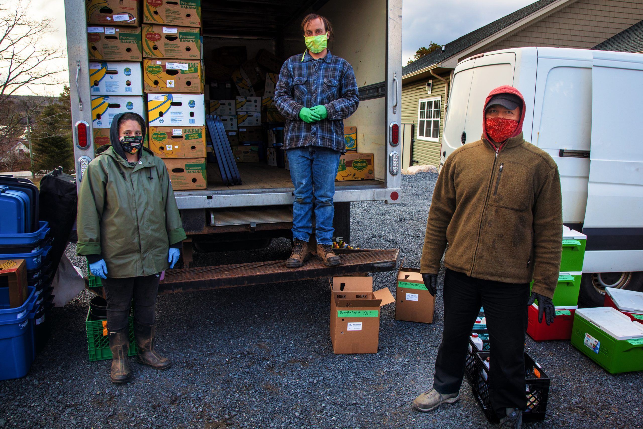 Three masked people by a truck with boxes for food pickup