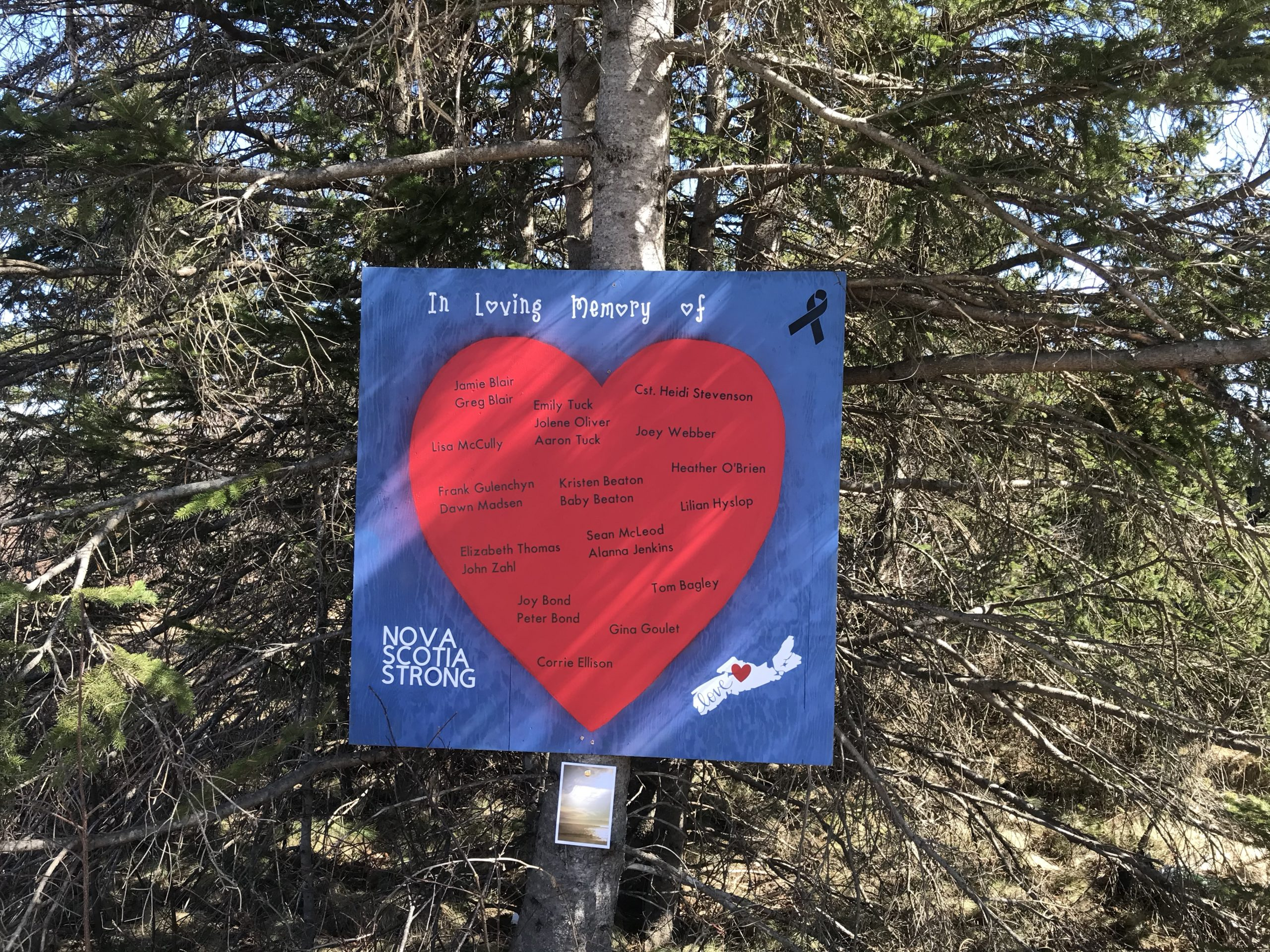 A poster at the roadside memorial in Portapique commemorates the 22 people killed in the mass shooting. It's a big red heart on a royal blue background, with the names of people written on it in black, and a small map of Nova Scotia with Nova Scotia Strong in white capital letters in the lower left corner.