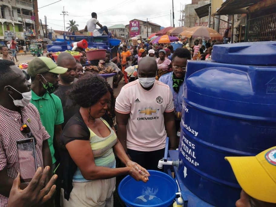 Citizens of Freetown crowd in for water distribution but wash hands first. Photo: Theophilus Gbenda