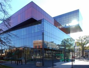 an exterior photo of the North East corner of the Halifax Central Library, in bright mid-afternoon sun, with the sunlight bouncing off and through the different coloured glass windows. You can see the reflections of the opposite buildings in the facade.