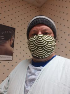Man in hospital gown and non-medical mask