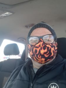 Man in a car wearing a mask with a flame pattern.