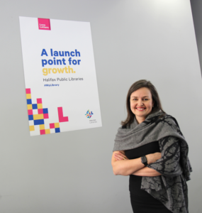 "Woman in front of a sign saying ""A launch point for growth"""