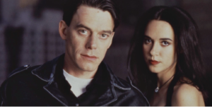 Man in leather jacket and woman look into camera