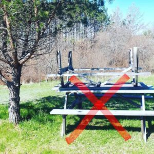 A picnic table upside-down on another table with a red X through them.