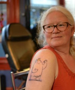 Woman in a tank top with a tattoo on her bicep.