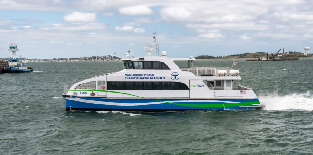 A photo of one of the fast ferries used in the Massachusetts Bay Transportation authority. It's sleek, it's got a deck for passengers and a bridge above it, with a little open area on the back. It looks like a mini-yacht.