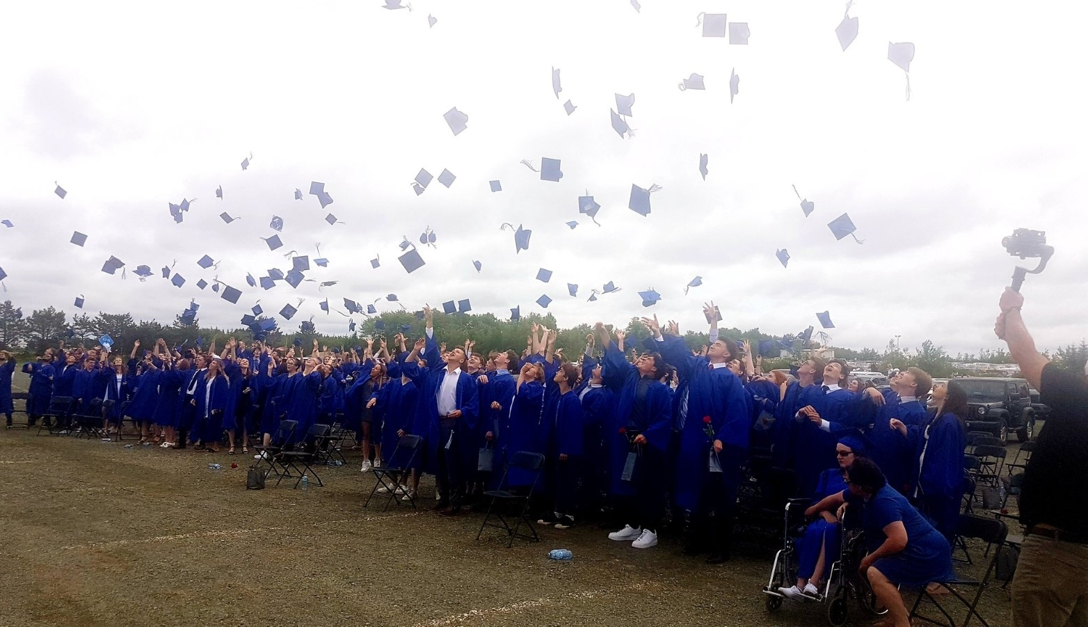 Outdoor graduation ceremony with people packed close together