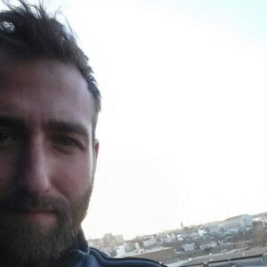A selfie of Tyler Ledden, with a view of the city behind him.
