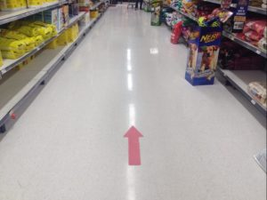 Photo of a dred direction arrow on the floor of a grocery store