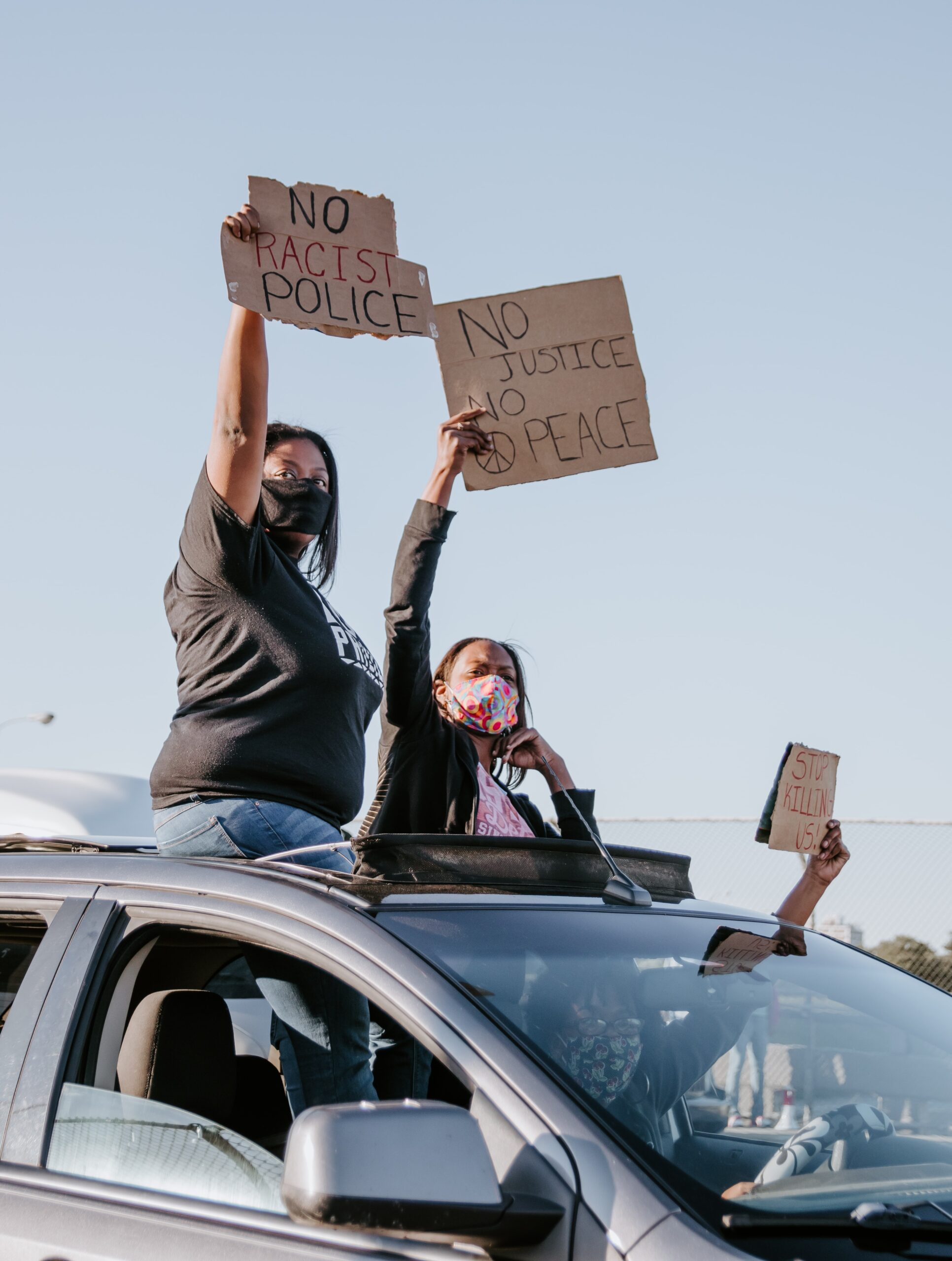 Women out the sunroof of a car with anti police brutality signs.