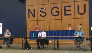 People socially distanced at tables under an NSGEU sign