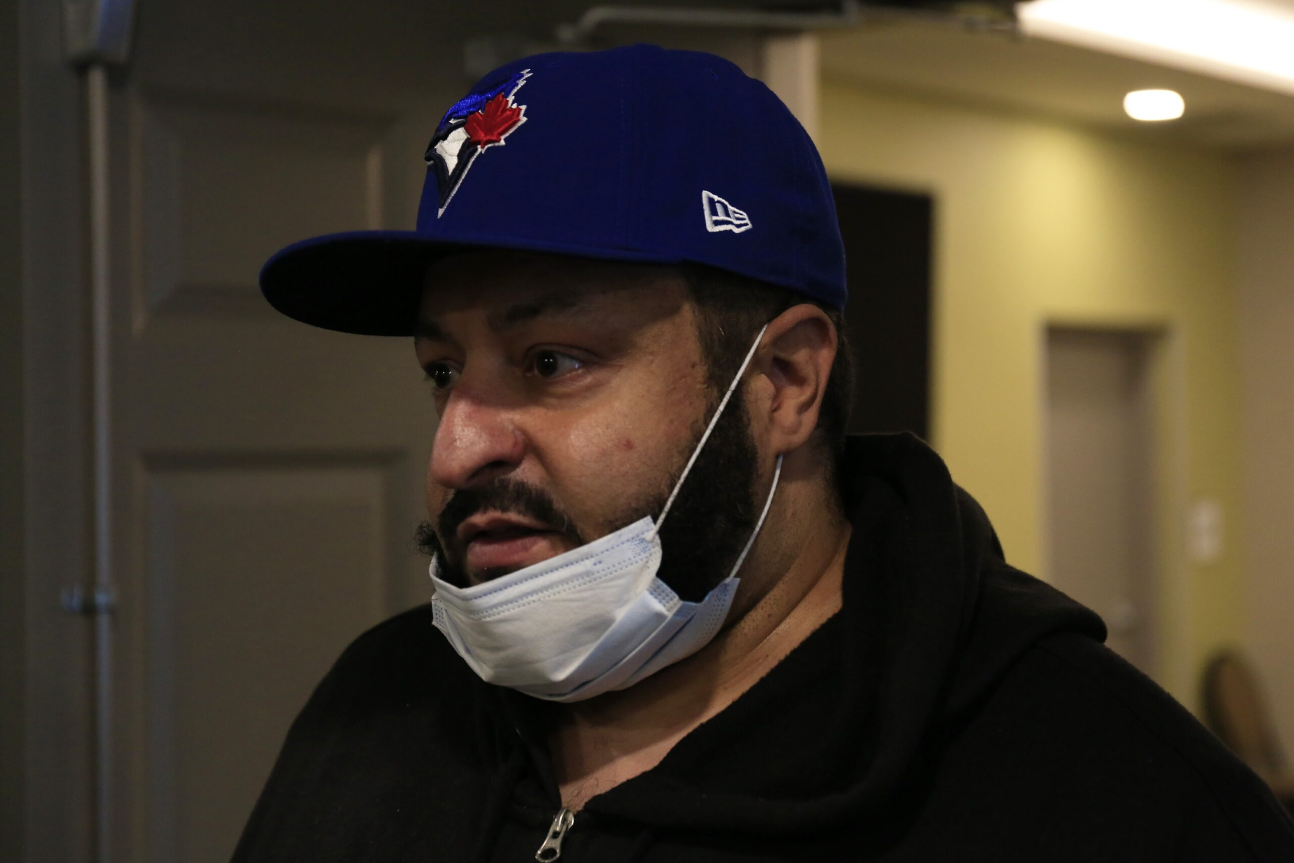 Bearded Black man in Blue Jays cap wearing a surgical mask slung under his chin.