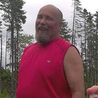Smiling man in a red muscle shirt outdoors.