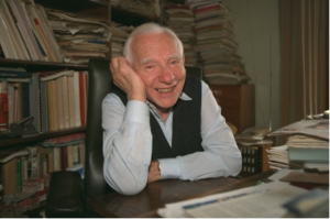 Smiling man at desk with bookshelves behind him.