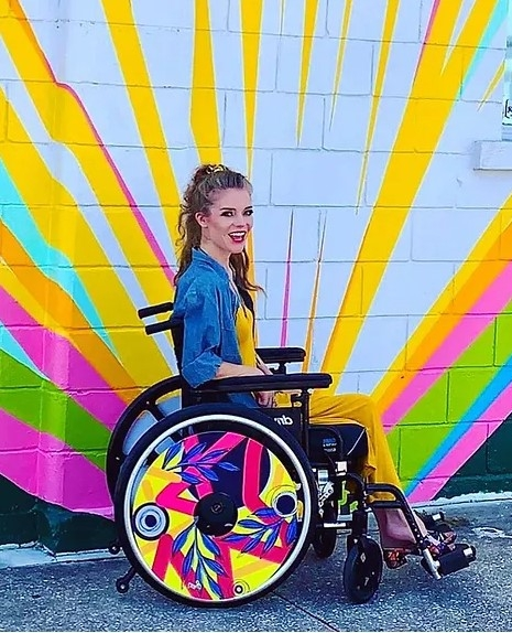 Fashionable young woman in front of an outdoor mural, in a wheelchair with colourful wheel covers