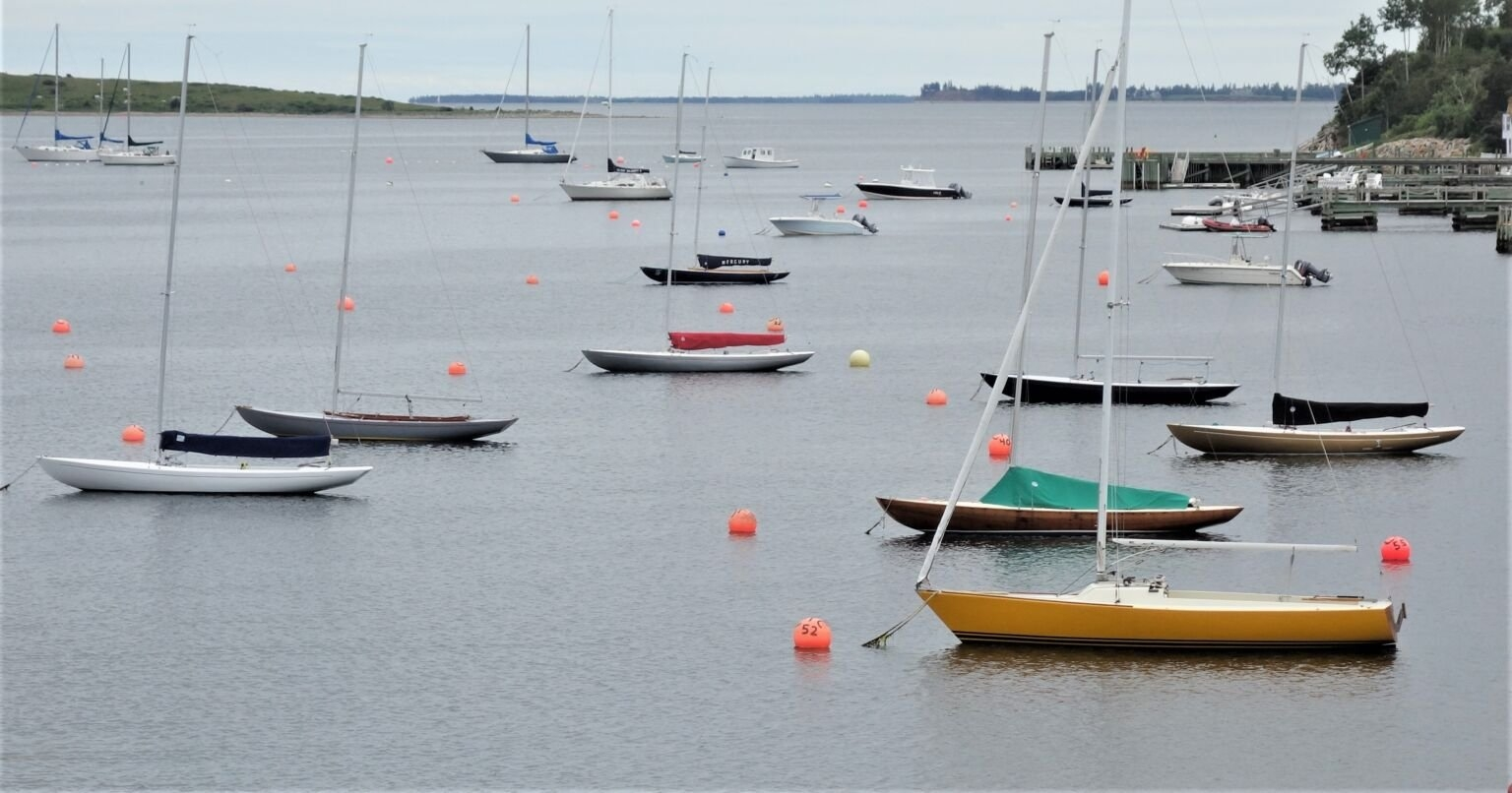 Small, colourful unrigged sailboats moored in a calm harbour
